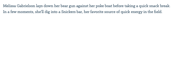 Melissa Gabrielson lays down her bear gun against her poke boat before taking a quick snack break. In a few moments, she'll dig into a Snickers bar, her favorite source of quick energy in the field.